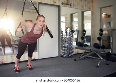 Young fit blond woman exercising with suspension bands in a modern gym in the morning