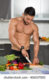 young fit bodybuilder in the kitchen, cooking, cutting vegetables