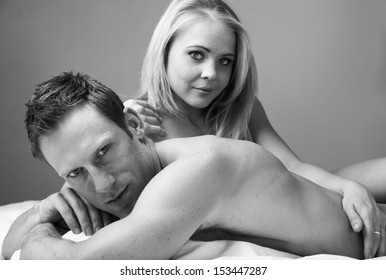 Young and fit caucasian adult couple lying on naked on a bed. Black and White.