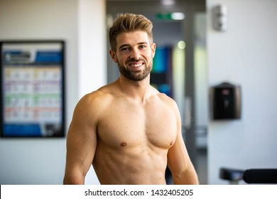 Young fit Caucasian man showing his good shape body with shirtless on gym background. Handsome man with smooth tan skin with happy face and nice chest and good muscle standing in the gym