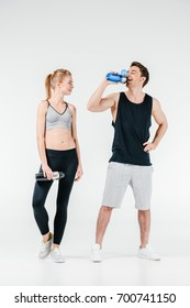 young fit couple with fitness shakers isolated on white