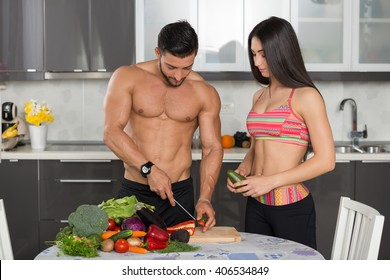 young fit couple in the kitchen, cooking, cutting vegetables