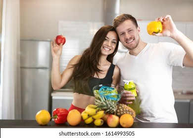 young fit couple man and woman standing in the kitchen full of fruits and vegetables, he holds pepper, she holds apple, nutrition and dietology.