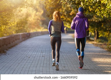 Young fit couple running in autumn park in the morning