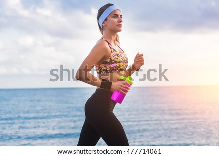 613b2a90cbe7 Young fit cute sporty girl in sportswear running on beach at sunset in  morning. Fitness