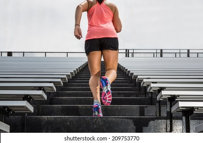 "Young fit female athlete running up bleachers at a stadium to illustrate ""challenge""."