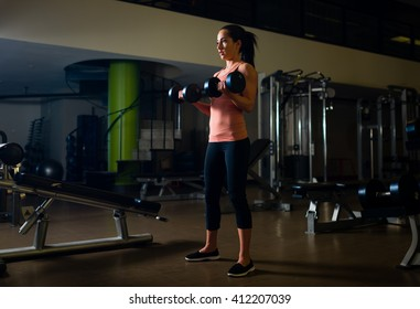 Young, fit female working out in a gym with dumbbells.