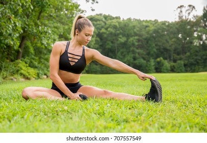 Young fit female in workout clothes stretching in the park.