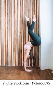 Young fit flexible woman wearing sportswear do handstand in modern living room. Indoors workout. Training at home.