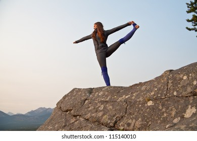 Young fit girl practicing yoga on a cliff over looking the colorful changing autumn leaves