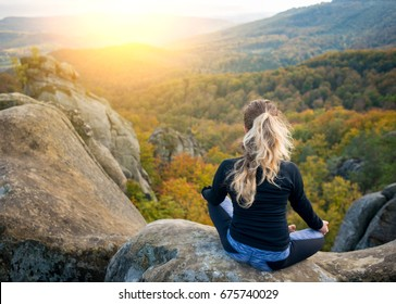 Young fit girl is practicing yoga and doing asana Siddhasana on the top of the high rocky mountain in the evening. Beautiful sunset, autumn forests, rocks and hills on the background