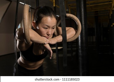 Young fit girl pulling up on a gimnastic rings