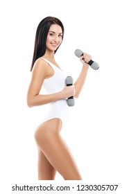 Young and fit girl pumping a dumbbells. Woman in sporty swimsuit. Sport, fitness and healthy lifestyle concept.
