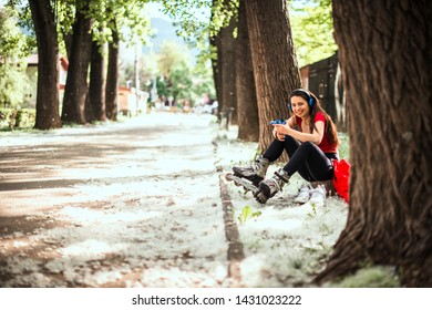 Young fit girl sitting on the ground in the park while listening music from headphones