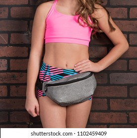 Young Fit Girl in Sportswear with a Gray Fanny Pack - Against a Brick wall