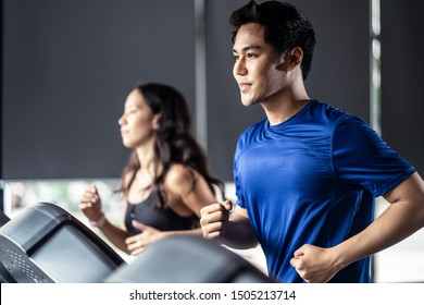 Young fit handsome Asian man and beautiful Asian woman running on treadmill or running machine in modern fitness gym. Seen from side view while they focusing on running. Workout in Gym and fitness.