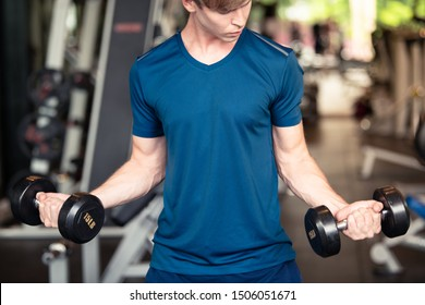 Young fit handsome Caucasian athlete man holding dumbbell for weight training at gym and fitness
