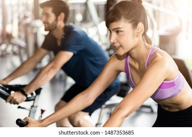 Young fit handsome Caucasian man and beautiful Asian woman cycling on bike machine in modern fitness gym. Seen from side view while they focusing on exercising. Workout in Gym and fitness for health.