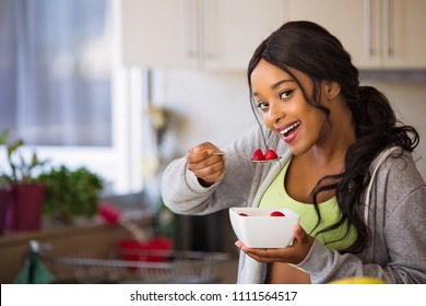 Young fit and healthy woman eats from a bowl of fruit with strawberries. She is dressed in sports wear ready for a workout. Very happy and lean with toned body. Smiling.