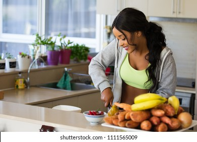 Young fit and healthy woman eats from a bowl of fruit with pears and strawberries. She is dressed in sports wear ready for a workout. Very happy and lean with toned body. Cooking in kitchen.