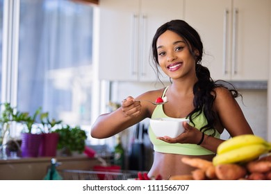 Young fit and healthy woman eats from a bowl of fruit with strawberries. She is dressed in sports wear ready for a workout. Very happy and lean with tones body. Smiling at camera.