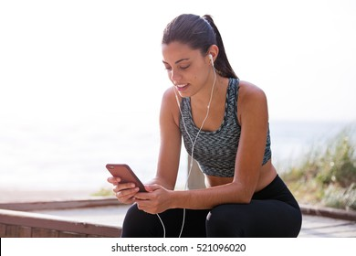 Young fit and healthy woman listening to music before doing some exercise in the great outdoors.