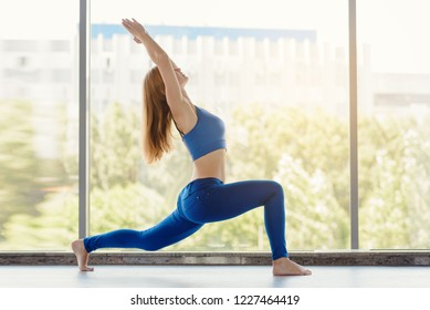 Young fit healthy woman practicing yoga on panoramic window background