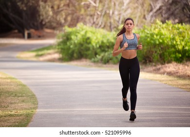 Young fit and healthy woman running down a footpath. Focus is soft and woman is in motion.