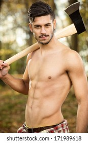 Young fit lumberjack holding an ax over his shoulder