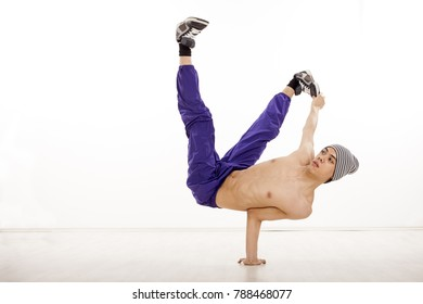 Young fit male dancer sitting on one hand, performing streetdance position  with legs up, wearing ultraviolet pants. Horizontal image with copyspace, in studio, on white background and wood floor.