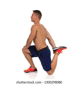 Young fit man in blue shorts and orange sneakers kneeling on one leg, stretching quadriceps muscle and looking away. Side view. Full length studio shot isolated on white.