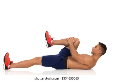 Young fit man in blue shorts and orange sneakers is lying on a floor, holding his knee and stretching gluteus maximus. Side view. Full length studio shot isolated on white.