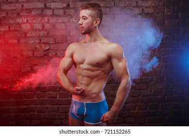 Young fit man bodybuilder with perfect big muscles posing over brick wall