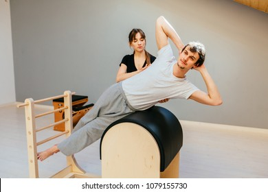 Young fit man is concentrated on exercising on pilates barrel with female instructor at gym. Sports equipment.Active and healthy lifestyle rehabilitation concept.