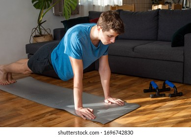 Young fit man is doing plank exercise at home. Stay home during COVID-19 quarantine  concept.