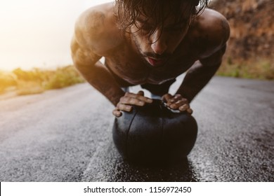 Young fit man doing push up on medicine ball. Fitness male exercising with a medicine ball on wet road outdoors.