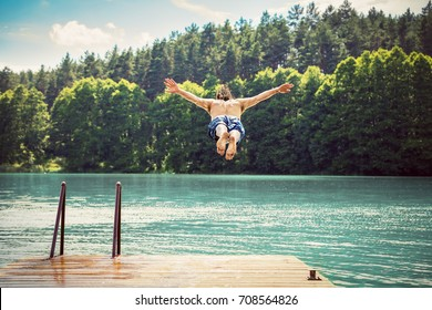 Young fit man making a jump into a lake from wooden jetty. Water sport. Nature and outdoor activity.