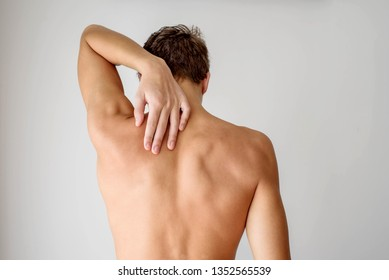 Young fit man standing with naked muscular back and touching his shoulder with the hand. Back pain and spine issues concept.