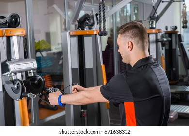 Young fit man training on row machine in gym room in fitness center