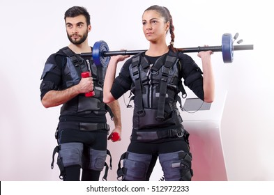 Young fit man and woman doing exercises in gym with electro muscle stimulation