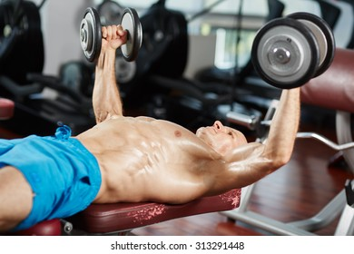 Young fit man working out at bench press with dumbbells