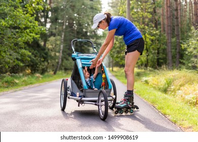 Young fit mother women skating outdoors with baby stroller