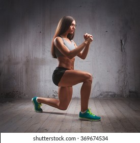 Young fit muscular woman doing lunge in brutal interior