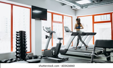 Young fit pretty woman doing exercises on the treadmill. Attractive sporty girl has hard and effective training on the track machine at the end of the gym. Back view