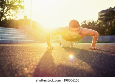 Young fit shirtless Caucasian man doing push-ups outdoors on sunny summer day. Fitness and sport lifestyle concept.