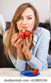Young, fit and slim, beautiful woman eating strawberries. Face expression - desire, reverie, pensiveness, thoughts. Romantic pose. Girl showing a heart done from two strawberries.