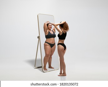 Young fit, slim woman looking at fat girl in mirror's reflection on white background. Thinking she's not enough sportive. Concept of healthy lifestyle, fitness, sport, nutrition and body positive.