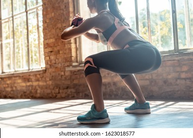 Young fit sporty active athlete woman wear sportswear crouching doing squats session fitness training legs buttocks muscles workout exercise in modern sunny gym space indoors, rear back close up view