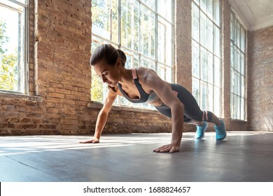 Young fit sporty active woman wear sportswear standing in plank pose doing yoga fitness training workout stretching core push up pushup exercise on wooden floor in modern sunny gym space indoors.