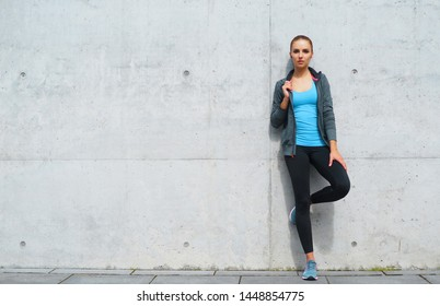 Young, fit and sporty brunette girl in sportswear. Woman doing sports outdoor.